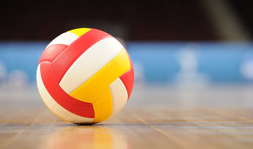 A volleyball on a wooden gym floor